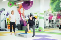 Trainer is showing work out to senior woman. Personal trainer is showing work out exercise with steps to senior woman Stock Photo