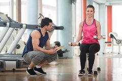 Personal Trainer Helping Woman On Biceps Exercise. Personal Trainer Showing Young Woman How To Train Biceps Exercise With Dumbbells In A Health And Fitness Royalty Free Stock Photo