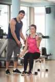 Personal Trainer Helping Woman On Biceps Exercise. Personal Trainer Showing Young Woman How To Train Biceps Exercise With Dumbbells In A Health And Fitness Royalty Free Stock Image
