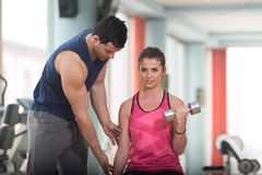 Personal Trainer Helping Woman On Biceps Exercise. Personal Trainer Showing Young Woman How To Train Biceps Exercise With Dumbbells In A Health And Fitness Royalty Free Stock Images
