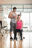 Personal Trainer Helping Woman On Triceps Exercise. Personal Trainer Showing Young Woman How To Train Triceps Exercise With Dumbbell In A Health And Fitness Royalty Free Stock Images