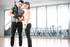 Personal trainer with suspension showing results to client. Personal trainer showing result of training plan to his female young client with suspension rope Stock Photo