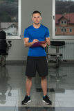 Personal Trainer Takes Notes On Clipboard Royalty Free Stock Photography
