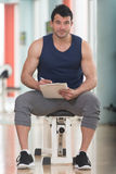 Handsome Personal Trainer With A Clipboard. Personal Trainer Takes Notes On Clipboard In a Gym Royalty Free Stock Photography