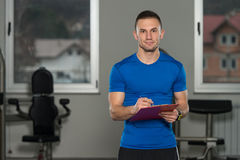 Personal Trainer Takes Notes On Clipboard Stock Images