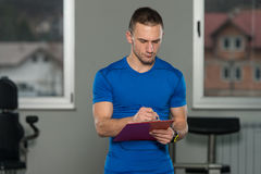 Personal Trainer Takes Notes On Clipboard Royalty Free Stock Images