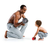 Personal trainer teaches his son how to lift dumbbells correctly Royalty Free Stock Image
