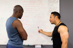 Personal trainer teaching. Professional personal trainer teaching men in fitness classroom Royalty Free Stock Photos