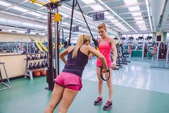 Personal trainer teaching to woman in suspension Stock Photo
