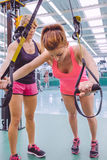 Personal trainer teaching to woman in suspension. Female personal trainer teaching to women in a hard suspension training with fitness straps on a fitness center Stock Images