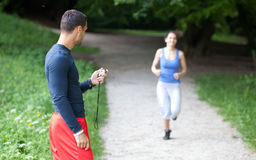 Personal trainer timing a female runner Royalty Free Stock Photography
