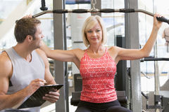Personal Trainer Watching Woman Weight Train Royalty Free Stock Photo