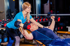 Personal trainer woman helping men working with heavy dumbbells. Stock Photo