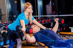 Personal trainer woman helping men working with heavy dumbbells. Stock Photos