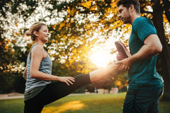 Personal trainer with woman stretching in park Stock Images