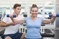 Personal trainer working with client on exercise ball Royalty Free Stock Photos