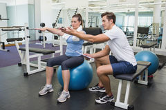 Personal trainer working with client on exercise ball Stock Images