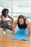 Personal trainer working with client on exercise mat stock image