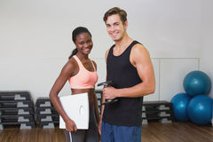 Personal trainer working with client holding scales Royalty Free Stock Images