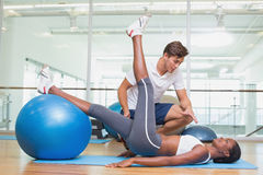 Personal trainer working with client using exercise ball Royalty Free Stock Image