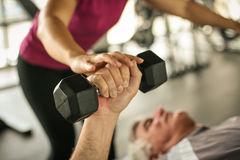 Personal trainer working exercise with senior man. Personal trainer working exercise with senior men in the gym. Man lift weight. Close up stock image