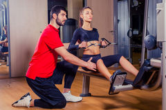 Personal trainer working with his client in gym Stock Image