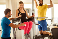 Personal trainer working with his client in gym. Gym,woman doing abdominal muscles with assisting her personal trainer Stock Photography
