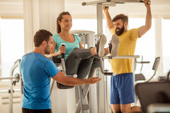 Personal trainer working with his client in gym. Gym,woman doing abdominal muscles with assisting her personal trainer Stock Image