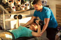 Personal trainer working with his client in gym Stock Photo