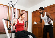 Personal Trainer Workout. A personal trainer encourages his student to work out harder. Working out on weight training equipment Stock Images