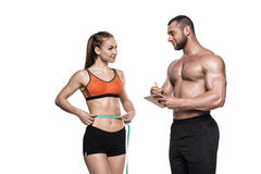Personal trainer writing in notepad while sportswoman measuring her waistline Royalty Free Stock Image