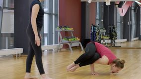 Personal trainer in yoga supports women in training on complex exercise. Fitness instructor watches as female beginner sportswoman performs stand on arms and stock video footage