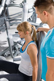 Personal trainer with young woman at gym Stock Image
