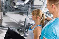 Personal trainer with young woman at gym Royalty Free Stock Photography