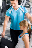 Personal trainer with young woman at gym Stock Photography