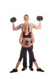 Personal Trainers. A team of personal trainers in the gym working out together. Man with dumbbells and woman with medicine ball royalty free stock photography