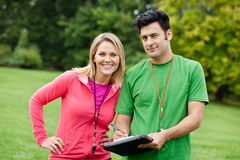 Personal trainers. Male and female personal trainers with whistles and clipboards at the park royalty free stock image