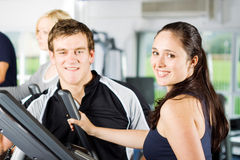 Personal trainers giving instruction. Personal trainers in the gym giving instruction and help to attractive young women Royalty Free Stock Photos