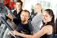 Personal trainers giving instruction. Personal trainers in the gym giving instruction and help to attractive young women stock images