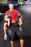 Personal training. A shot of a male personal trainer assisting a woman lifting weights Stock Images