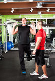 Personal training. A shot of a male personal trainer assisting a male athlete training Stock Photos