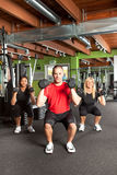 Personal training. A shot of a male personal trainer training with two female athletes in the gym Stock Images