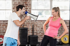 Personal trainor motivating his client with megaphone. In crossfit gym Royalty Free Stock Photo