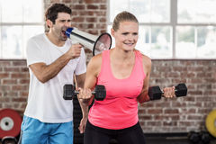 Personal trainor motivating his client with megaphone. In crossfit gym Stock Image