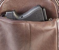 Personal Weapon in Purse. Photo of modern personal weapon in woman brown leather handbag Stock Image