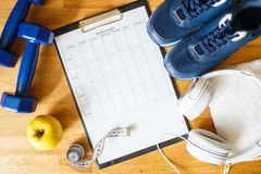 Personal workout plan with sneakers and dumbbells Stock Photos