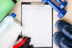 Personal workout plan with sneakers and dumbbells Royalty Free Stock Image
