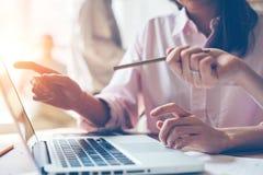 Personale addetto al programma che discute business plan Computer portatile sulla tavola, ufficio dello spazio aperto immagini stock