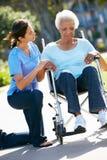 Personale che dispensa le cure che spinge donna maggiore infelice in sedia a rotelle Fotografia Stock Libera da Diritti