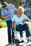 Personale che dispensa le cure che spinge donna maggiore in sedia a rotelle Immagine Stock